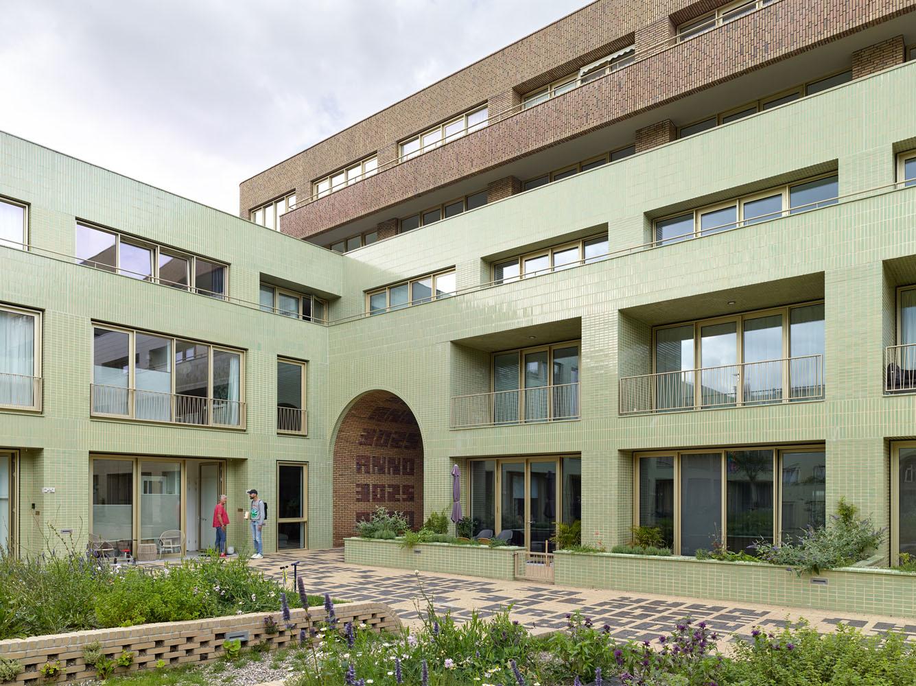 green glazed brick lines the courtyard facade