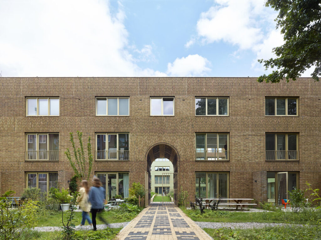The entryway and garden of the 80-unit apartment complex in Amsterdam with brick artwork on the path.