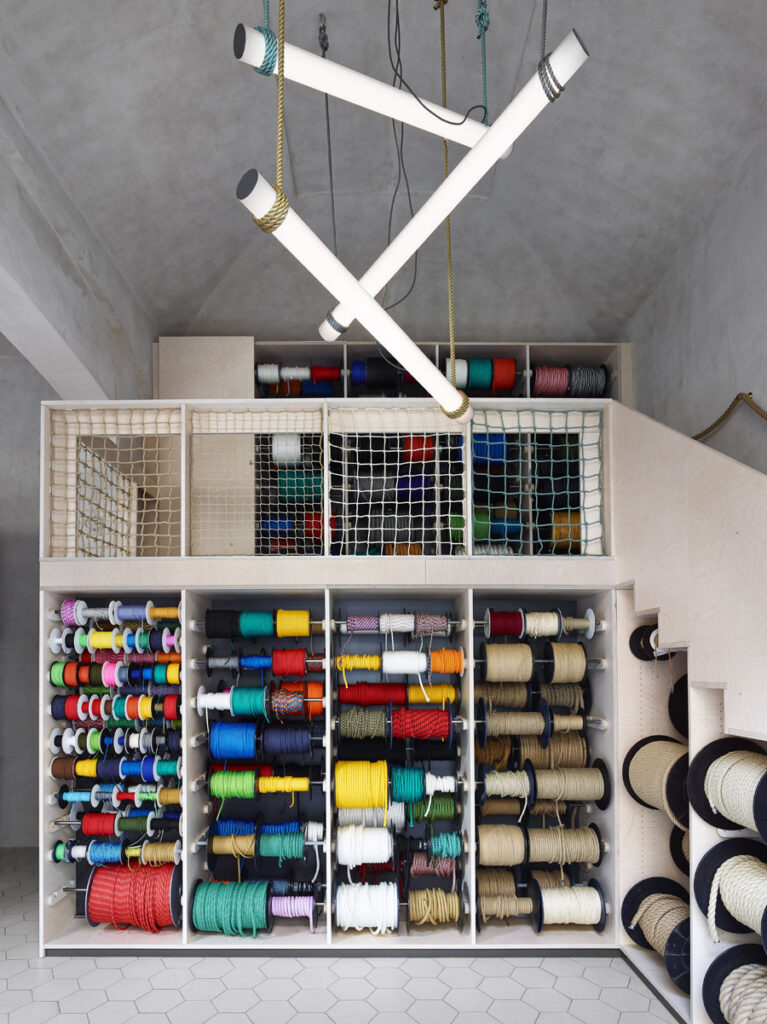 An interior view of a rope shop in Prague featuring a colorful display of ropes and a custom chandelier in the center of the concrete room.