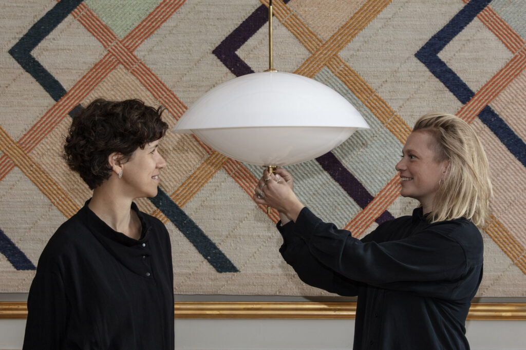designers stand on either side of an oblong light fixture.