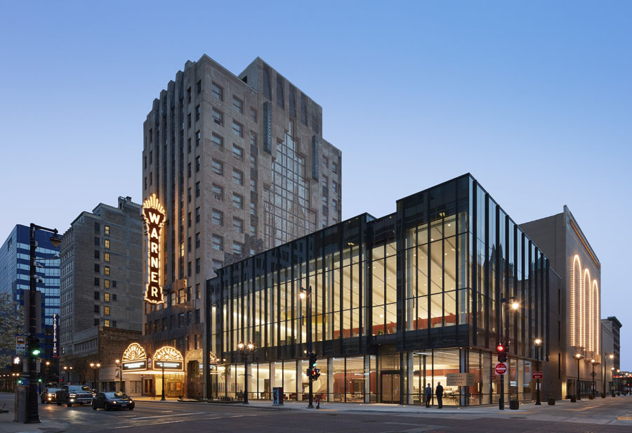 Exterior street view of Kahler Slater's renovation of the Warner Grand Theatre, now the Bradley Symphony Center. On a street in Milwaukee at dusk the Art Deco building sits next to a modern glass addition.