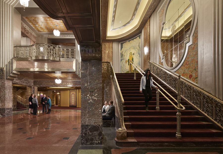 Grand art deco staircase leading up to the symphony hall with mirrored wall details, marble walls and gold hand rails.