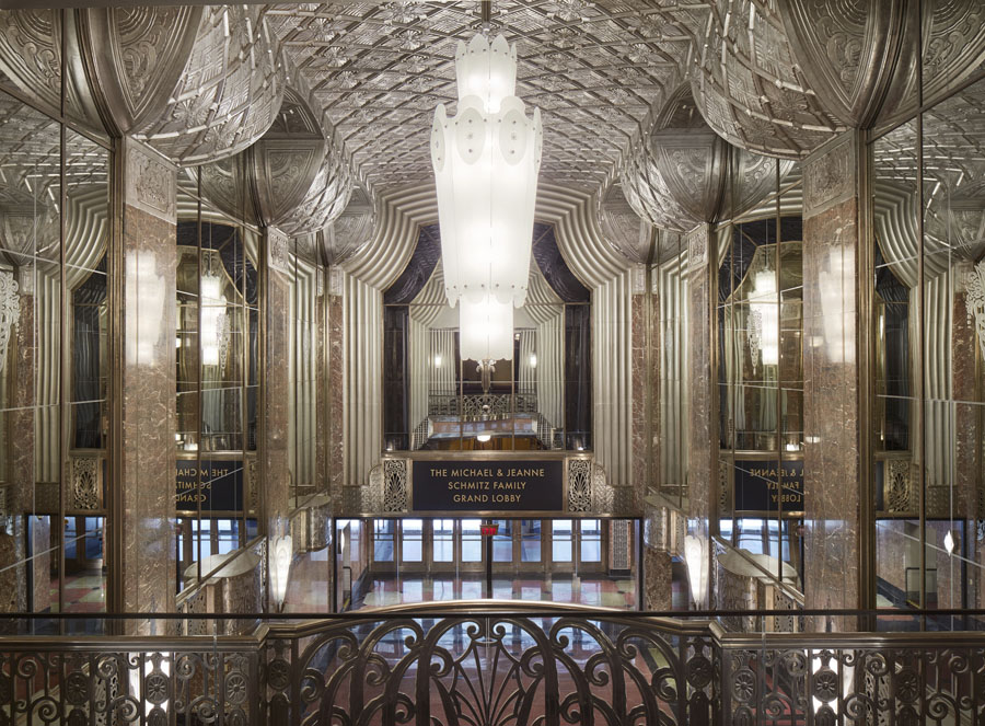 Interior of a grand atrium lobby looking down from a second floor mezzanine of a symphony hall with mirrored wall details  and a large central chandelier.