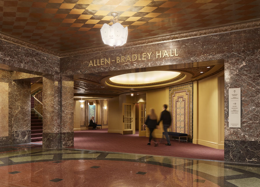 """Entrance to a symphony with text on a marble wall that reads """"Allen-Bradley Hall"""". The space has a checkered ceiling and tiled stone floor."""