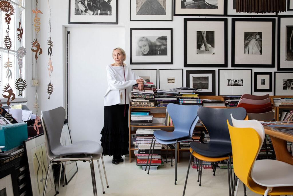 Carla Sozzani in a studio alongside several colorful Series 7 chairs.