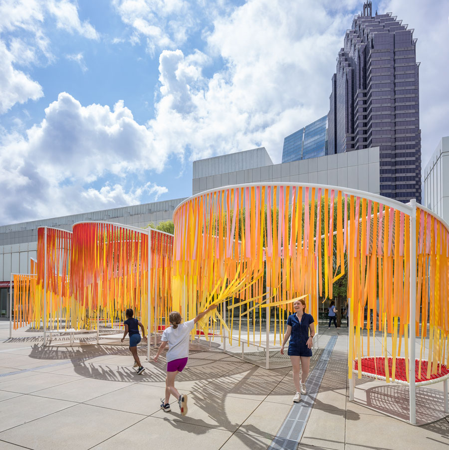 Byrony Robert's Outside the Lines installation sits in a plaza in front of Atlanta's High Museum of Art in the background. Kids are playing with the strands.