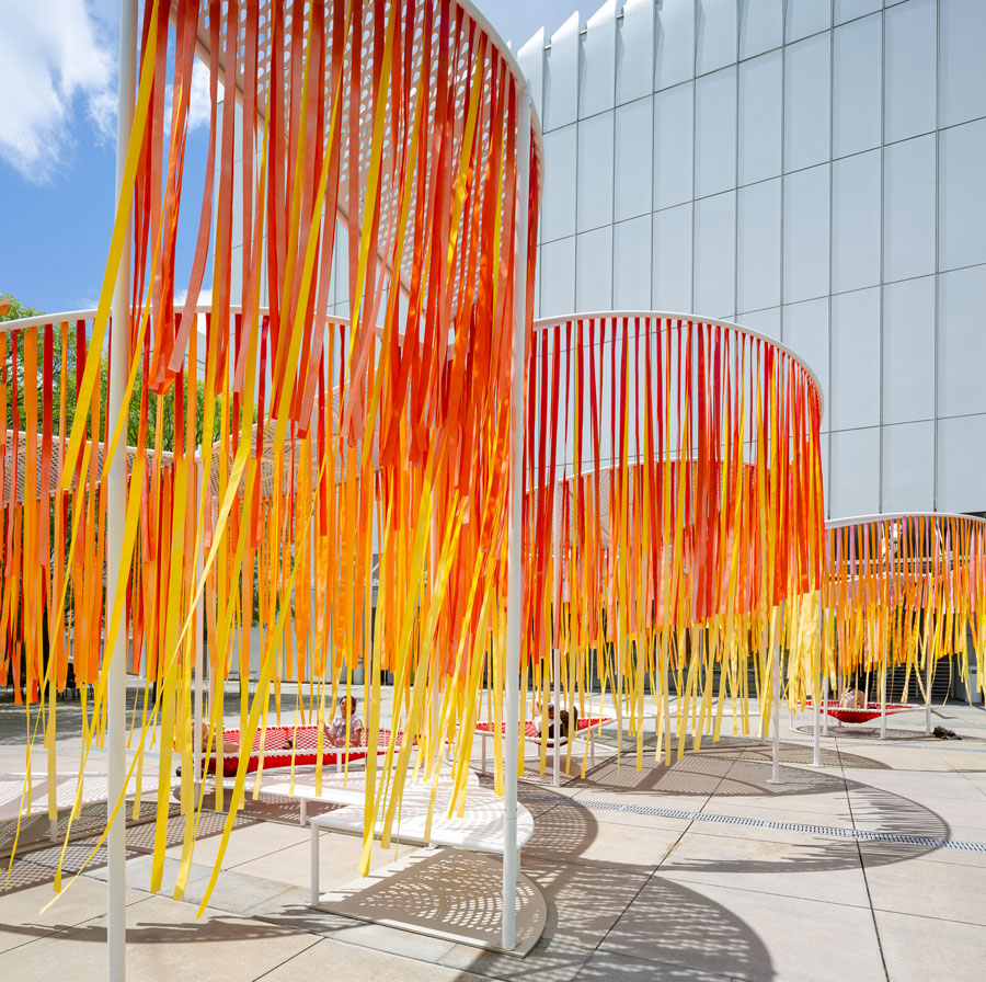 A close up of the orange and red strands hanging from Byrony Robert's Outside the Lines Installation at the High Museum in Atlanta.