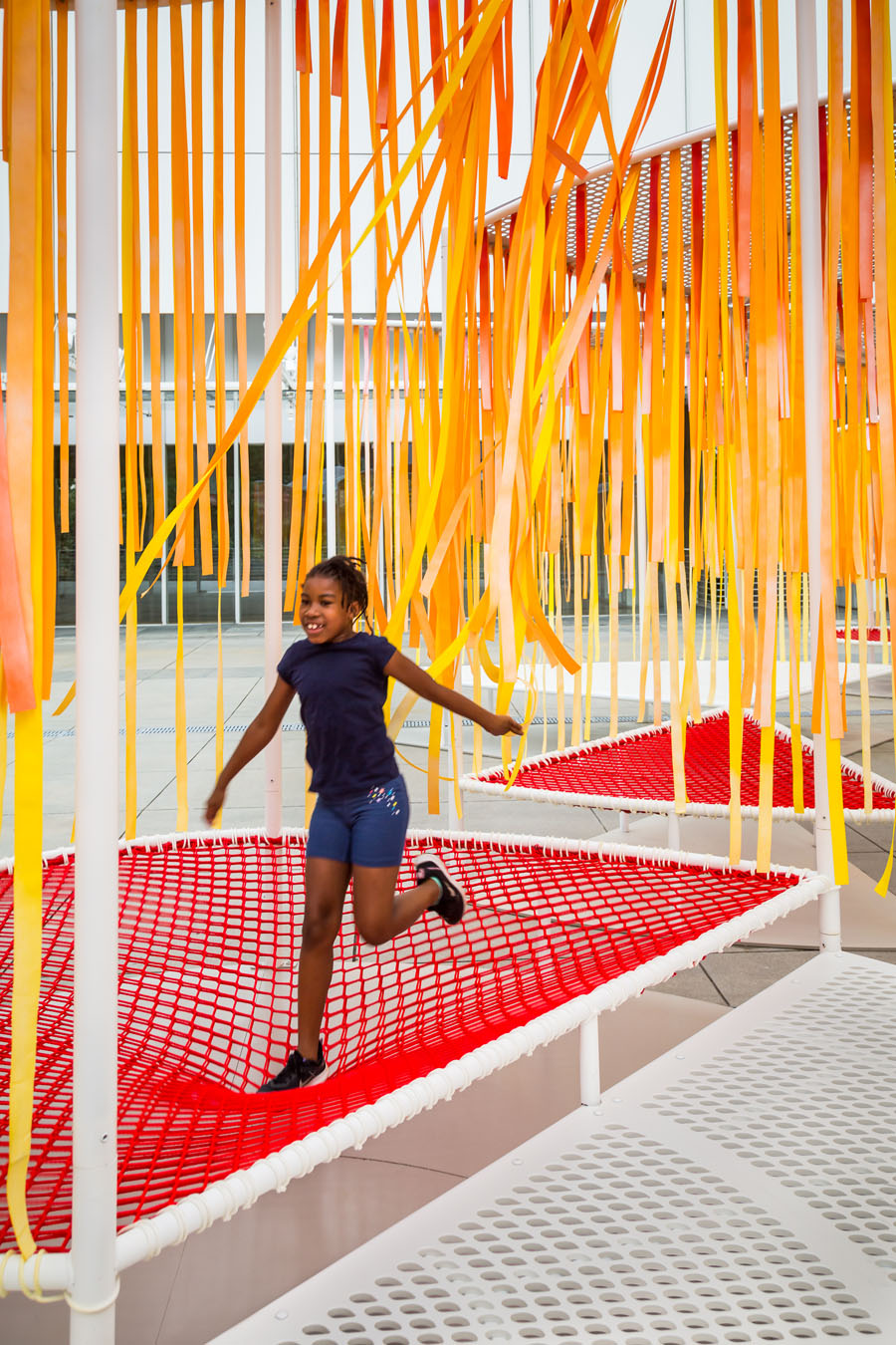 A young girl jumps on a mesh trampoline section of Byrony Robert's Outside the Lines installation at the High Museum in Atlanta, Georgia.