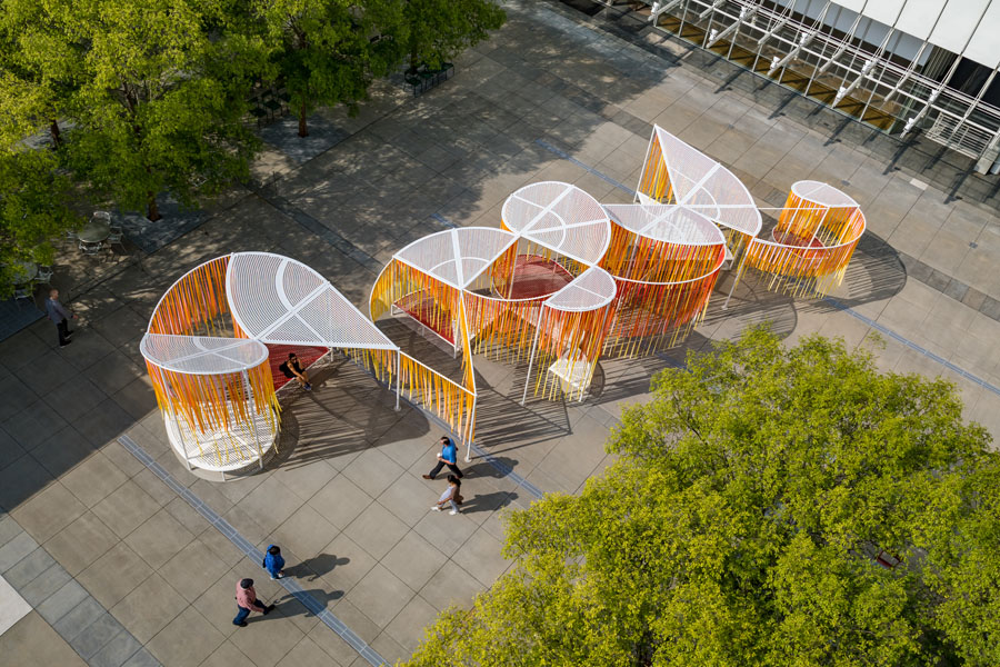 Aerial view of an orange and white installation in a concrete plaza outside of the High Museum of Art in Atlanta with people walking by.