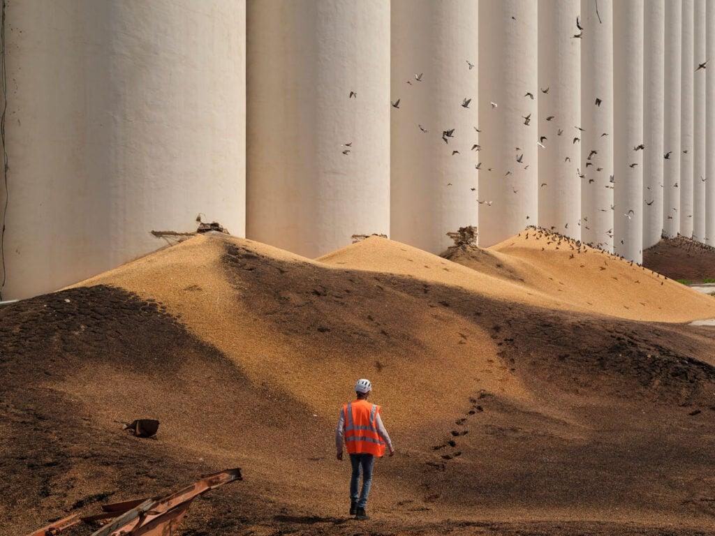 An emergency worker walks through mountains of grain spilling from broken silos