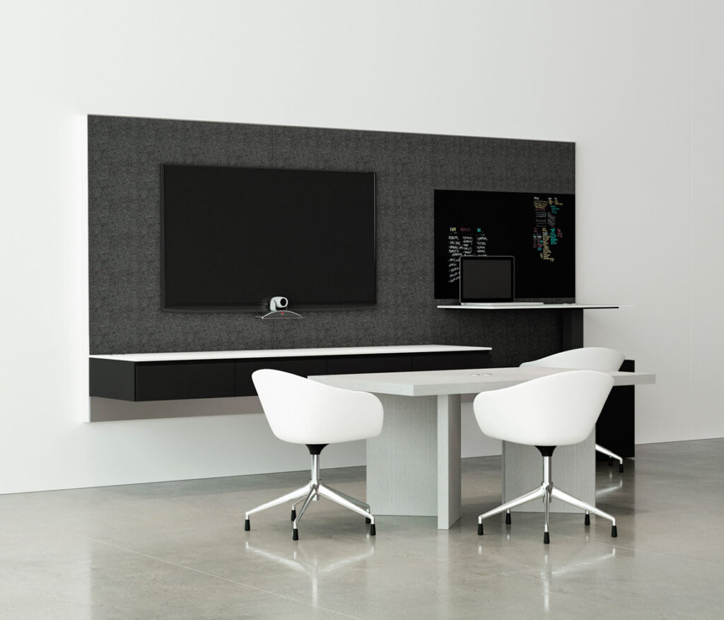 a conference table sits in front of a wall with a large monitor and visible webcam.