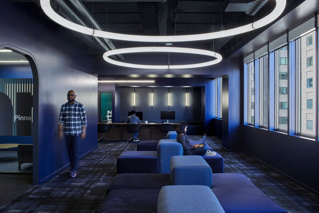 A workplace with circular overhead lights, blue walls, blue furniture, and large windows.