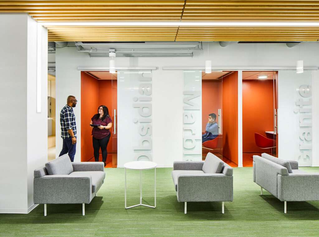 An office with open work areas and couches, as well as private meeting rooms.