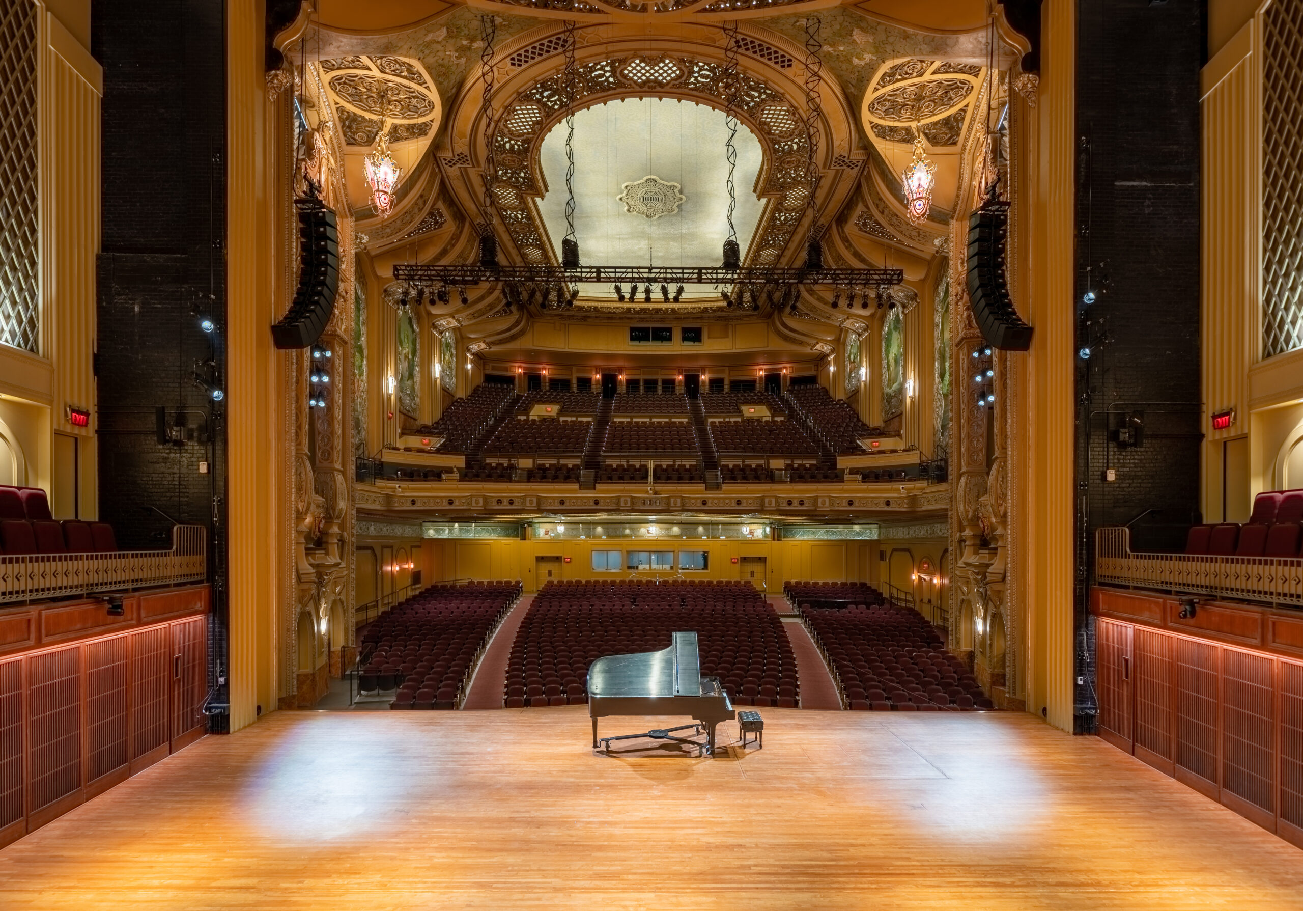 The interior of a grand art deco symphony hall looking out at the seating from the stage.