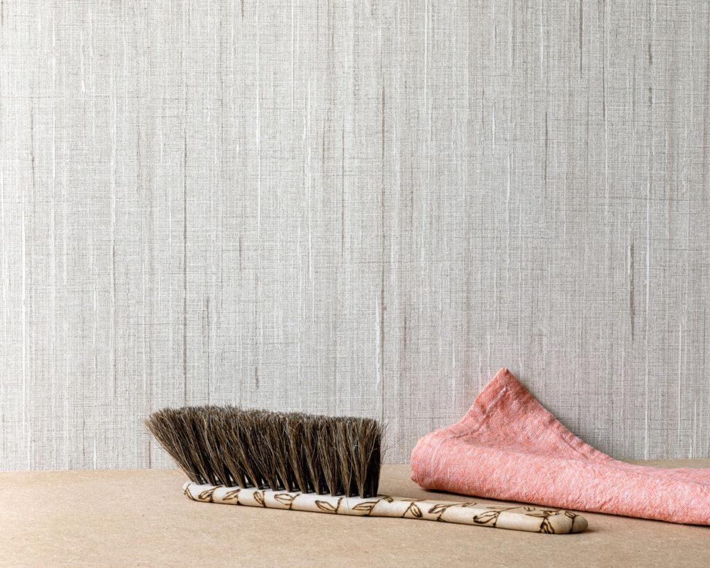 A brush sits in front of a fabric wallcovering.