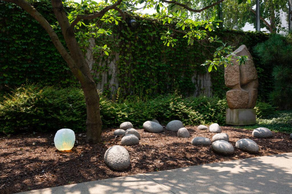 Objects of common interest designs placed near Isamu Noguchi sculptures in the Noguchi Museum Garden.