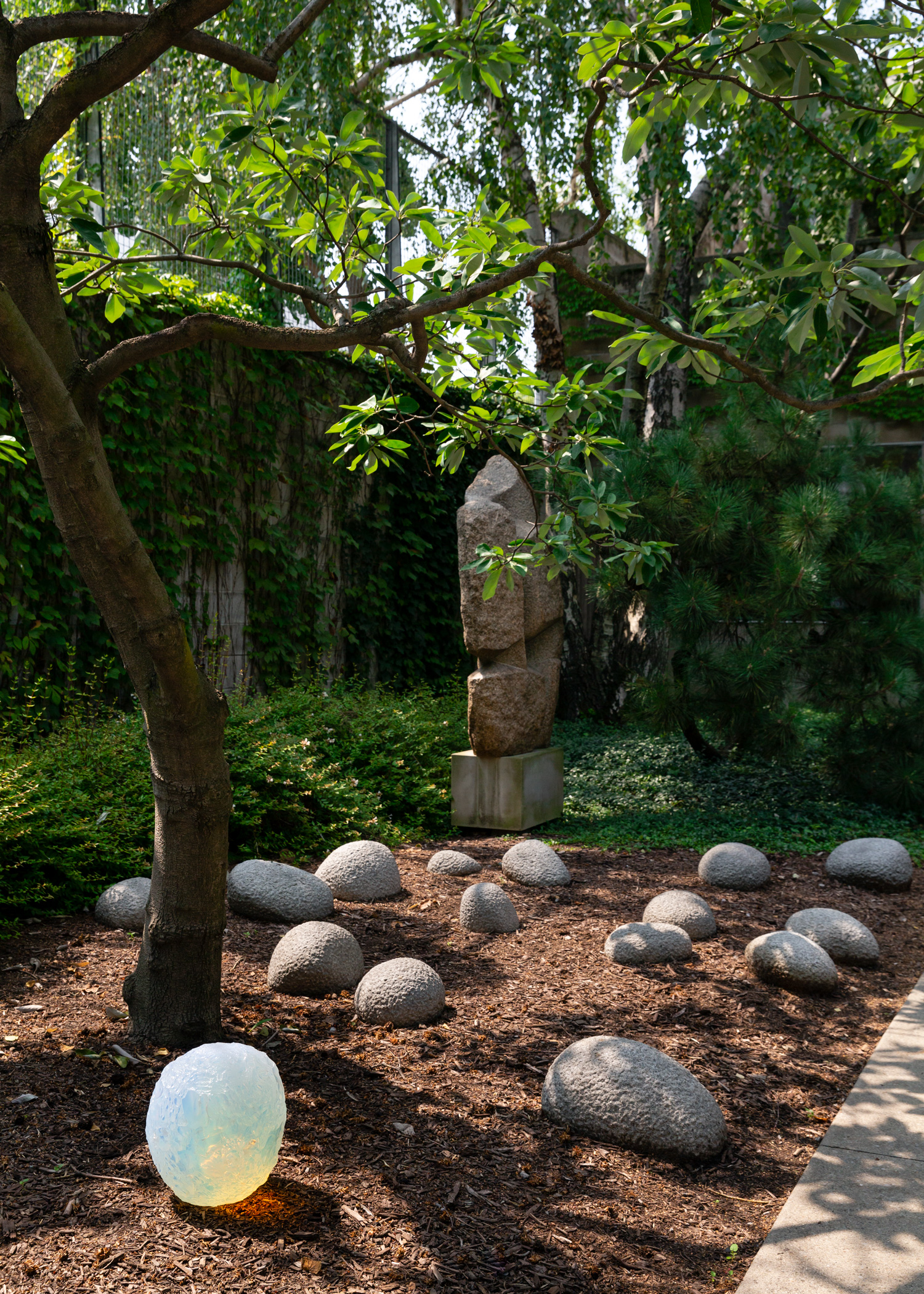 Sculptures by Objects of Common Interest interacting with Isamu Noguchi in the Noguchi Museum's garden.