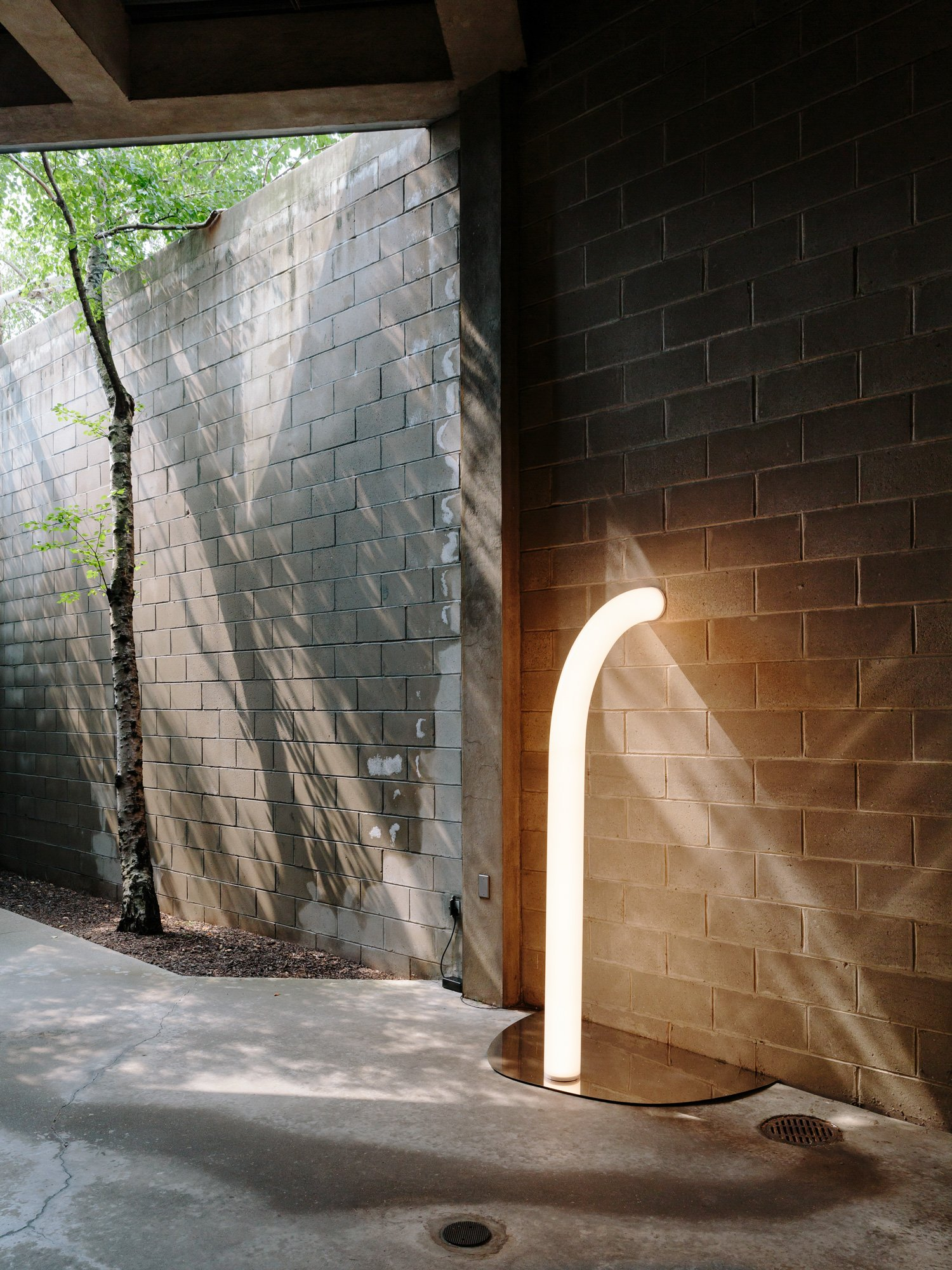 A tube light sculpture by Objects of Common Interest on a mirrored surface on the concrete floor of an outdoor gallery at the Isamu Noguchi Museum.