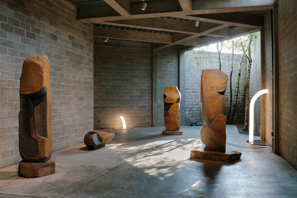 Light sculptures and stone sculptures sitting on the floor of a concrete open air gallery with trees growing in the corner.