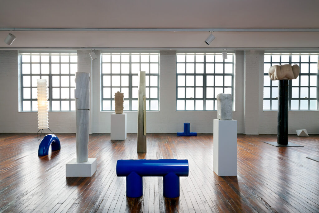 Various sculptures placed no podiums or on the wood floor in a gallery with large industrial windows in the background.
