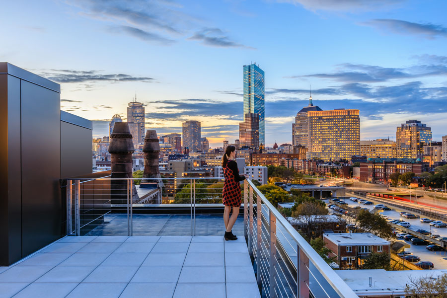 A person stands on a rooftop balcony overlooking the city of Boston.
