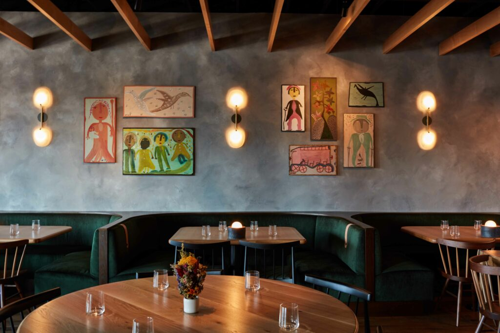 interior of restaurant with green booths and art on the walls