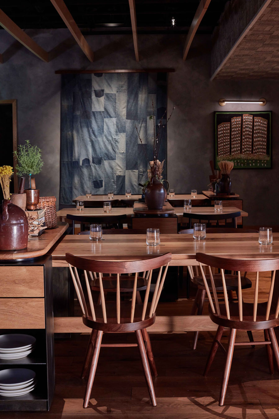 interior of restaurant showing wood tables and chairs and quilt hanging on wall