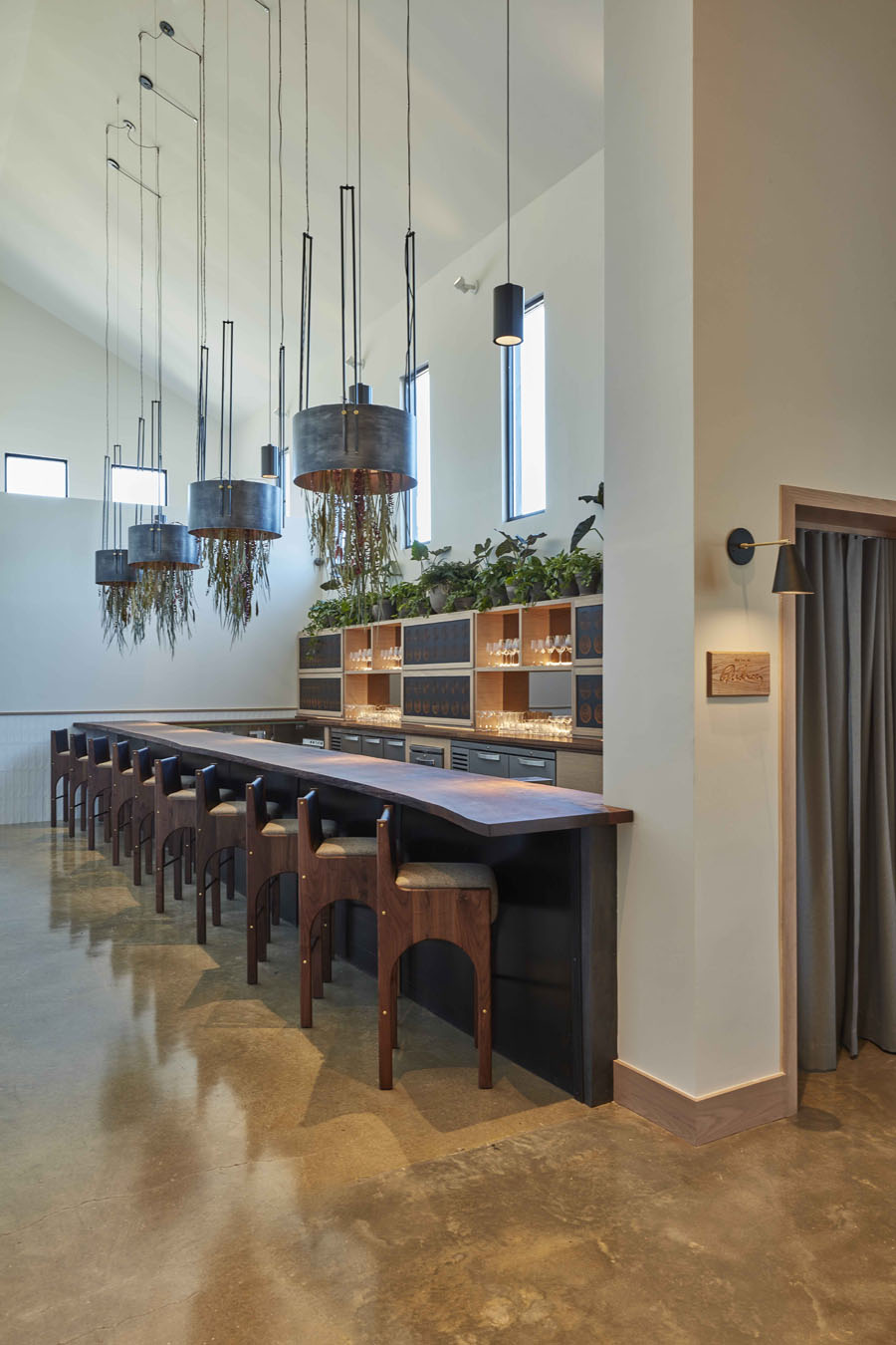 interior of restaurant showing bar seating and hanging herbs and lighting