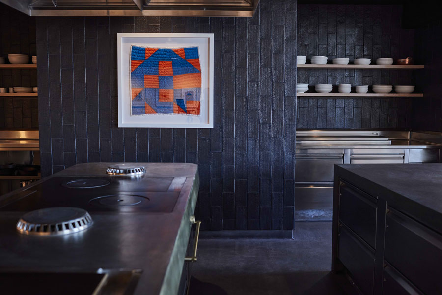 interior of kitchen in restaurant with framed quit hanging on walls