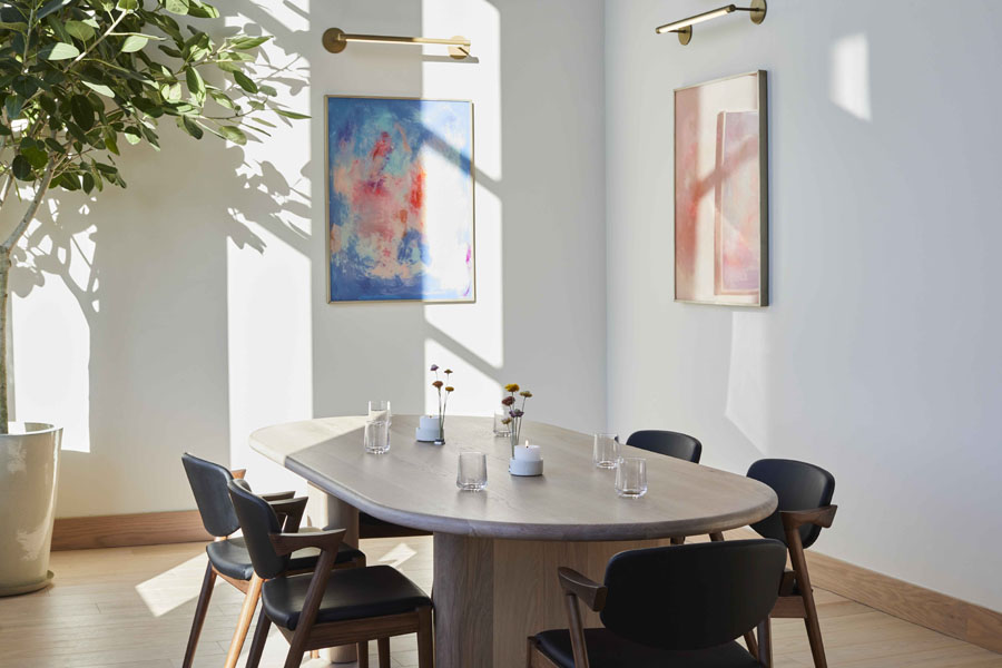 interior of restaurant with art hanging on white walls and potted plant in corner