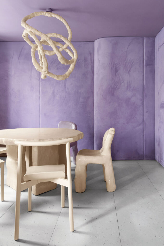 a table and chairs in a purple room
