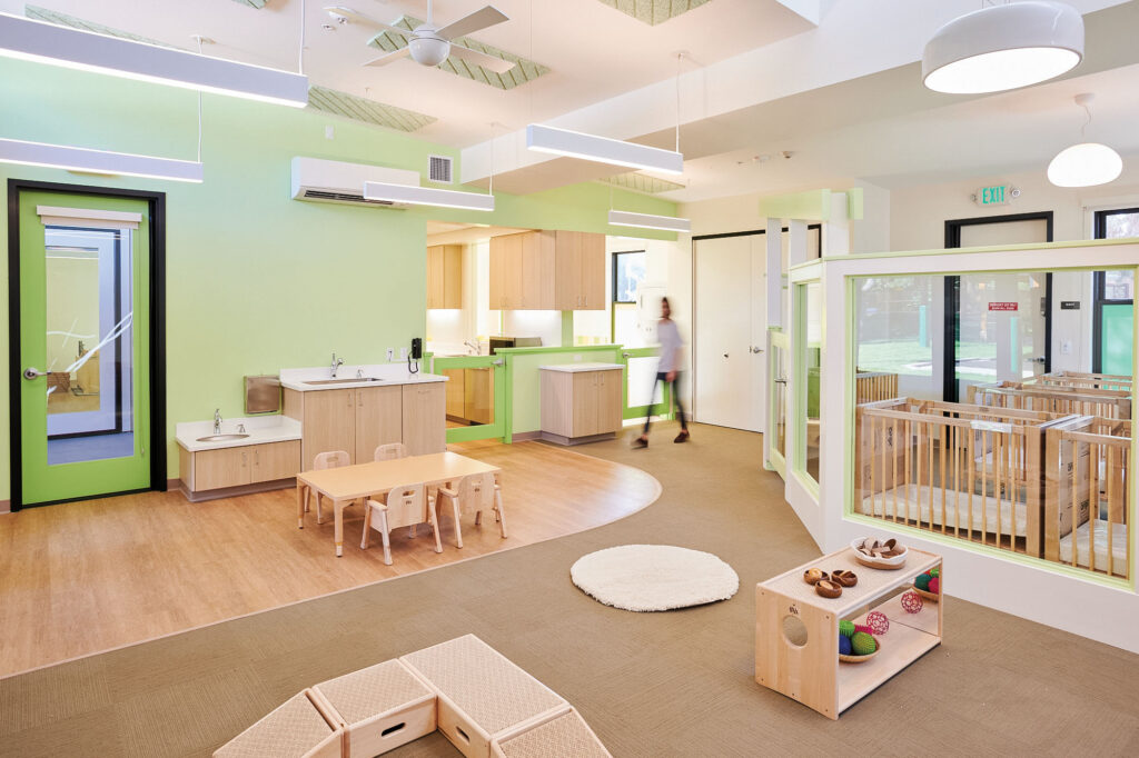 Daycare interior with green walls and wooden furniture