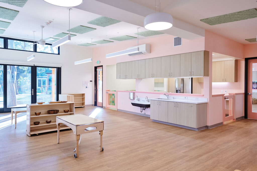 Daycare interior with pink walls ad wooden furniture